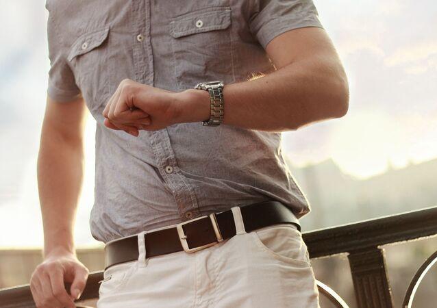 Un señor espera mirando su reloj