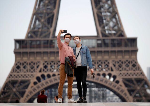 Una pareja con mascarillas cerca de la Torre Eiffel