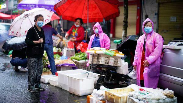 Vendedores de un mercado en Wuhan visten equipos de protección durante la crisis por COVID-19 - Sputnik Mundo
