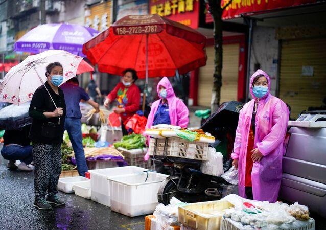 Vendedores de un mercado en Wuhan visten equipos de protección durante la crisis por COVID-19
