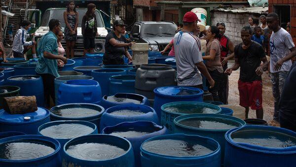 La gente llena los envases plásticos con agua en Petare, Caracas - Sputnik Mundo