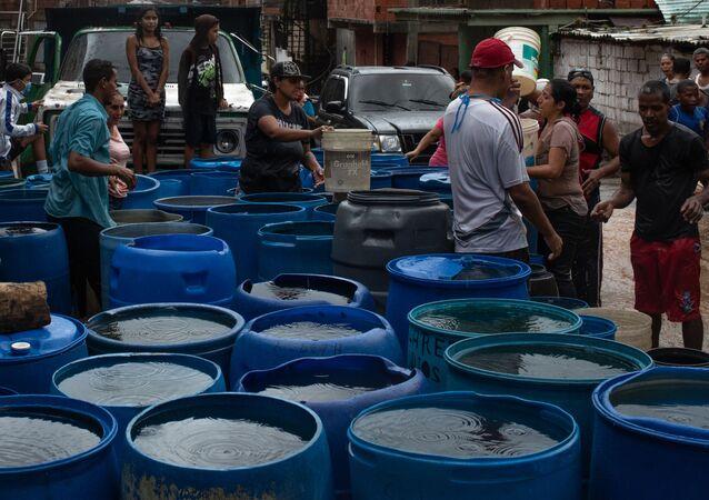 La gente llena los envases plásticos con agua en Petare, Caracas