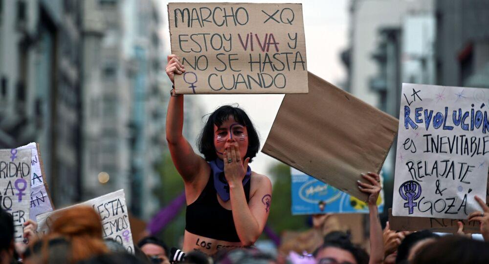 Mujer sostiene un cartel contra los feminicidios durante la marcha del 8 de marzo de 2020 en Montevideo