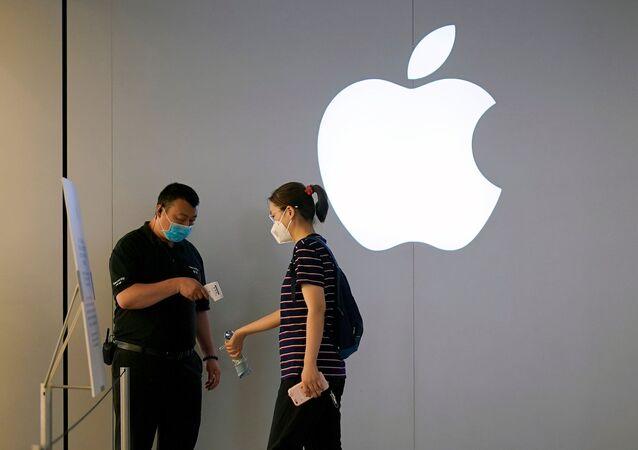 Logo de la compañía tecnológica Apple y dos personas con mascarillas