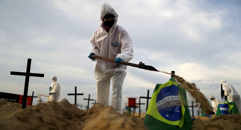 Activistas de la ONG Río de Paz con equipo de protección cavan tumbas en la playa de Copacabana