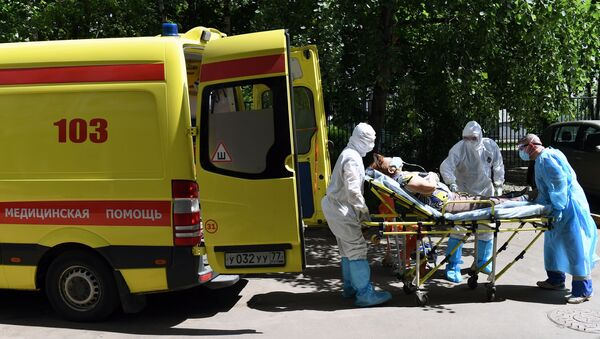 El personal de una ambulancia traslada a un paciente sospechoso con coronavirus en Moscú - Sputnik Mundo