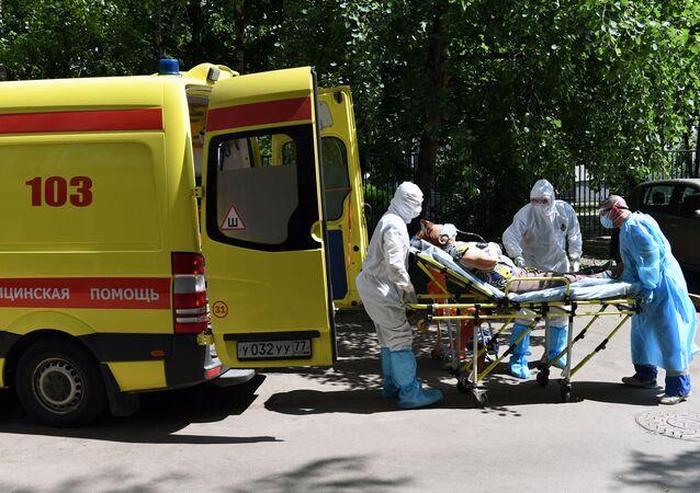 El personal de una ambulancia traslada a un paciente sospechoso con coronavirus en Moscú