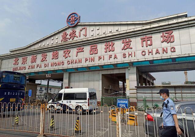 Un policía con una mascarilla fuera de una entrada del mercado mayorista de Xinfadi