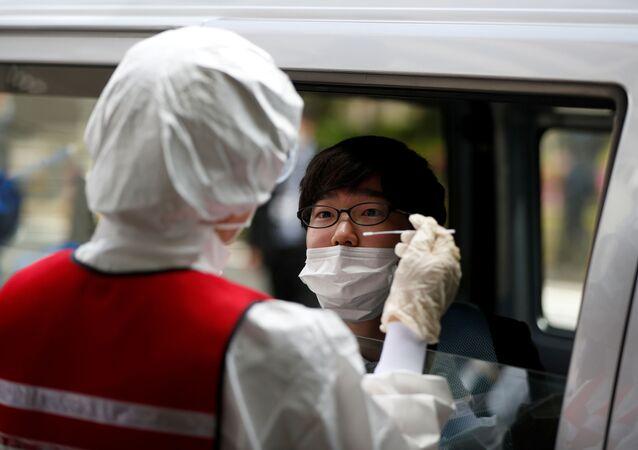 El personal médico toma una muestra para detectar el coronavirus en Tokio