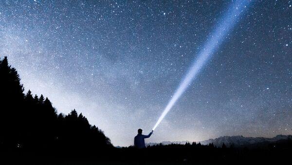 Una persona sostiene una linterna hacia el cielo - Sputnik Mundo