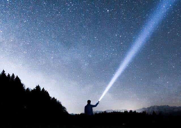 Una persona sostiene una linterna hacia el cielo