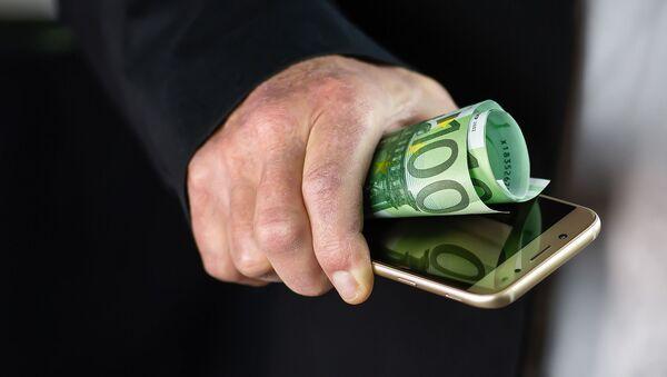Una persona sostiene un movil y algunos billetes - Sputnik Mundo
