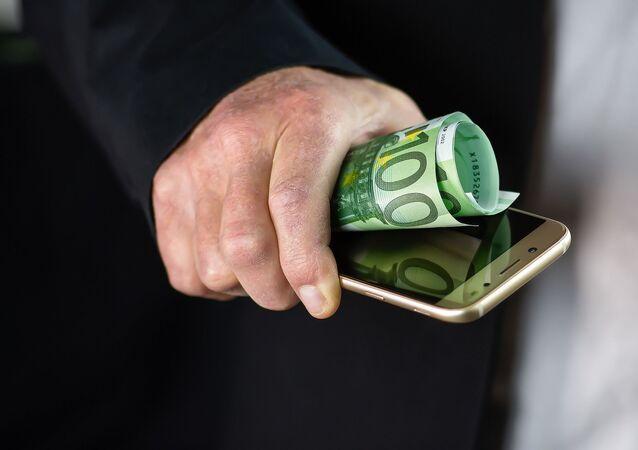 Una persona sostiene un movil y algunos billetes