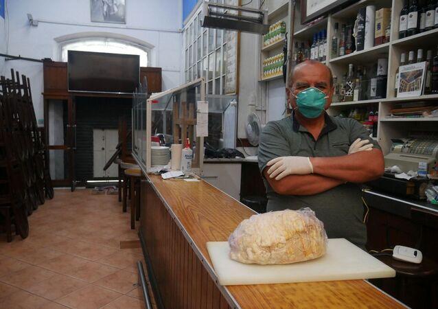 César Casusol, dueño del bar Juanito de Lima, con un jamón típico peruano