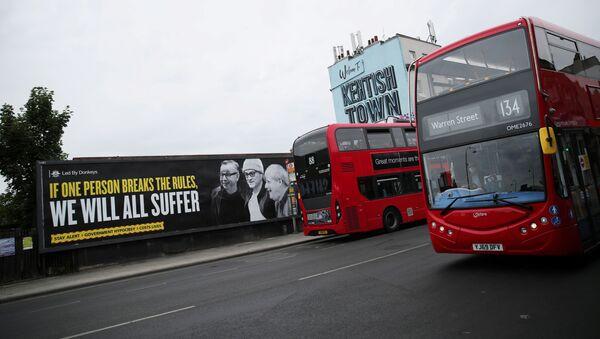 Una pancarta con las imágenes de Michael Gove, Dominic Cummings y Boris Johnson en Londres - Sputnik Mundo
