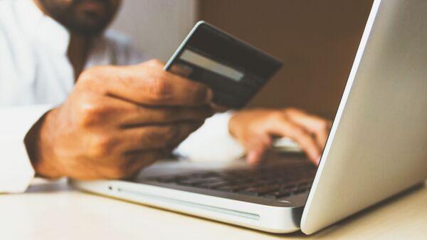 Un ordenador y una tarjeta de crédito (imagen referencial) - Sputnik Mundo