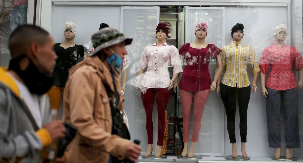 Colombianos caminan frente a tienda de ropa en Bogotá