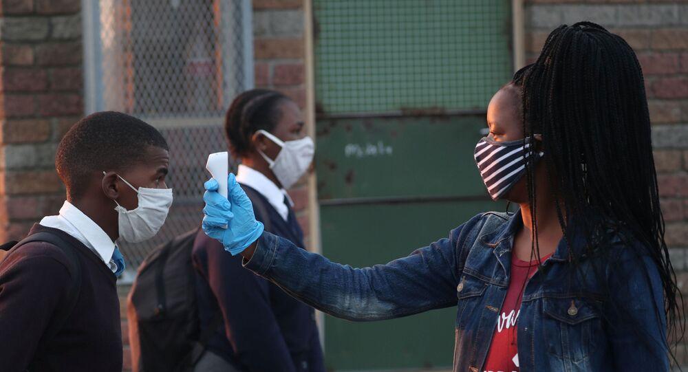 Una maestra mide la temperatura a un alumno en Sudáfrica
