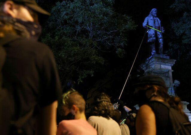 Manifestantes intentando derribar la estatua del general confederado Albert Pike.