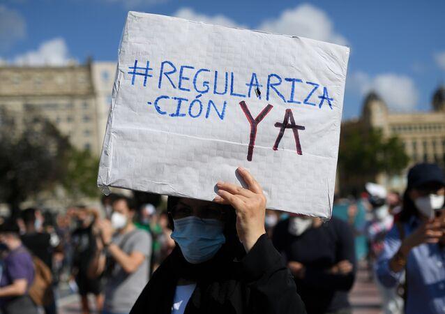 Un hombre sostiene una pancarta durante la manifestación por los migrantes en Barcelona el 20 de junio