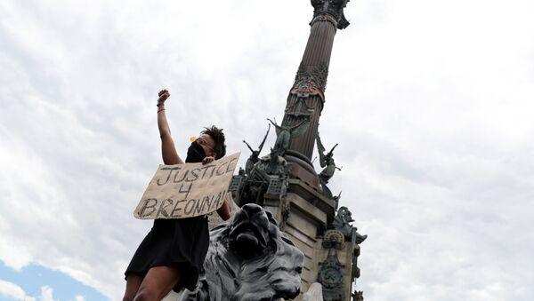 Un manifestante cerca de una estatua de Cristóbal Colón en Barcelona, España - Sputnik Mundo