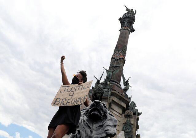 Un manifestante cerca de una estatua de Cristóbal Colón en Barcelona, España