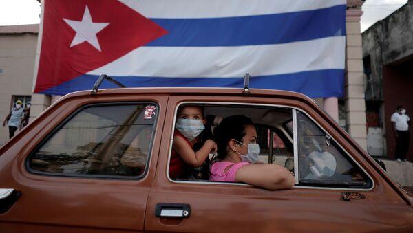 Dos persona el un coche y una bandera de Cuba - Sputnik Mundo