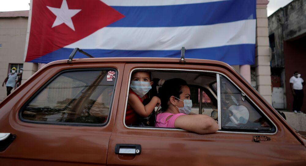 Dos persona el un coche y una bandera de Cuba