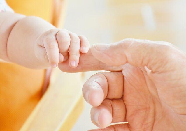 Imagen referencial de un bebé sujetado a la mano de un adulto