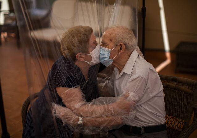 Agustina Cañamero y Pascual Pérez se abrazan y besan a través de una pantalla de plástico en un hogar de ancianos en Barcelona, España. 22 de junio de 2020
