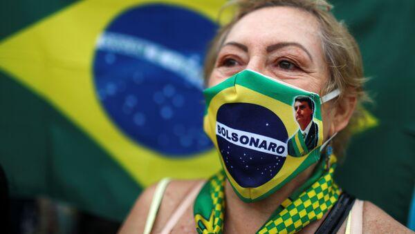 Una mujer brasileña con una mascarilla con la imagen de Bolsonaro - Sputnik Mundo