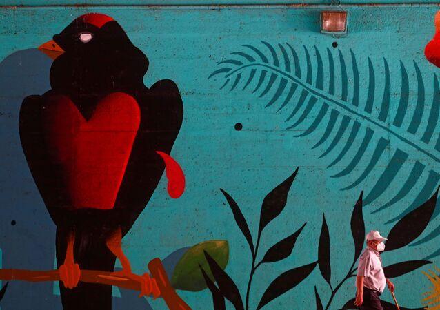 Un hombre en mascarilla pasa al lado de un muro con graffiti en Madrid