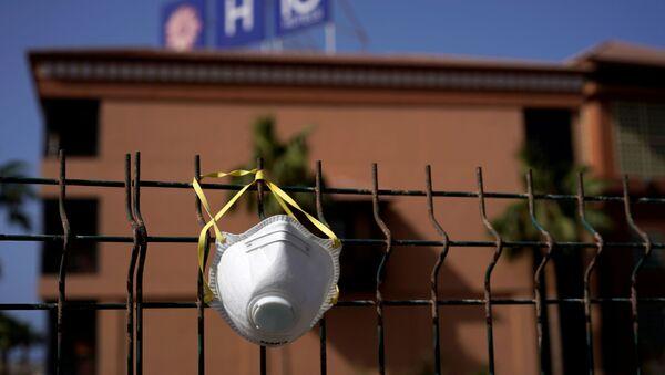Una mascarilla colgada en una cerca - Sputnik Mundo