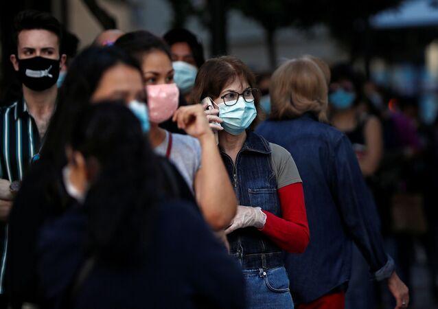 Personas con mascarillas faciales hacen cola para ingresar en una tienda de Madrid