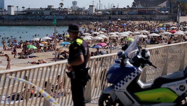 Un oficial de policía observa cómo la gente disfruta en la playa - Sputnik Mundo