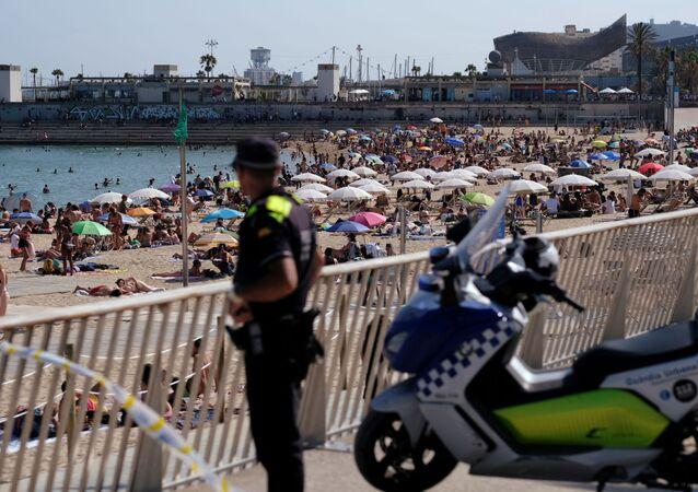 Foto de archivo: Un oficial de policía observa cómo la gente disfruta en la playa. Barcelina, 21 de junio de 2020