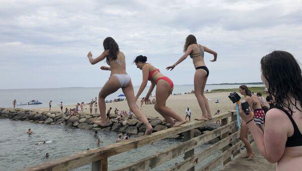Девушки прыгают с моста в пруд в Эдгартауне, штат Массачусетс - Sputnik Mundo