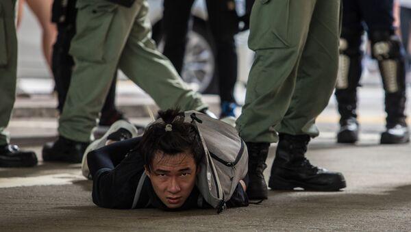 Задержанный полицией участник акции протеста против нового закона о национальной безопасности в Гонконге - Sputnik Mundo