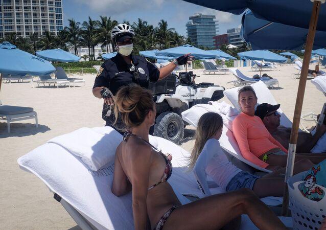 Una oficial de la policía habla con unos playeros en plena epidemia de COVID-19
