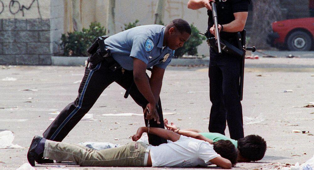 Un agente de Policía detiene a dos sospechosos de saqueo durante los disturbios de Los Ángeles