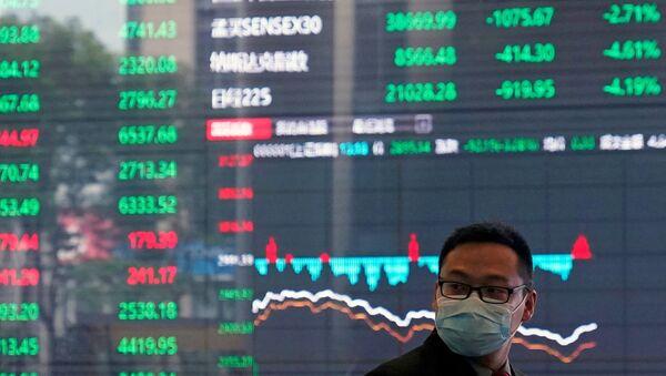Un comerciante ante una pantalla de la bolsa de Shanghái  - Sputnik Mundo