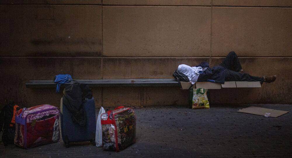 Un hombre duerme en una plaza en Lleida, España, el jueves 2 de julio de 2020