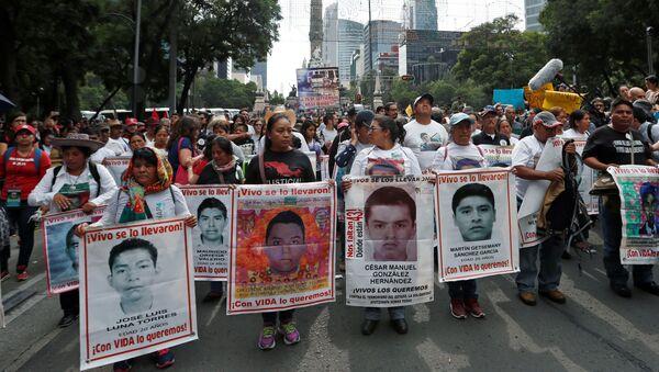 Los parientes sostienen carteles con fotos de estudiantes desaparecidos en una manifestación en México - Sputnik Mundo