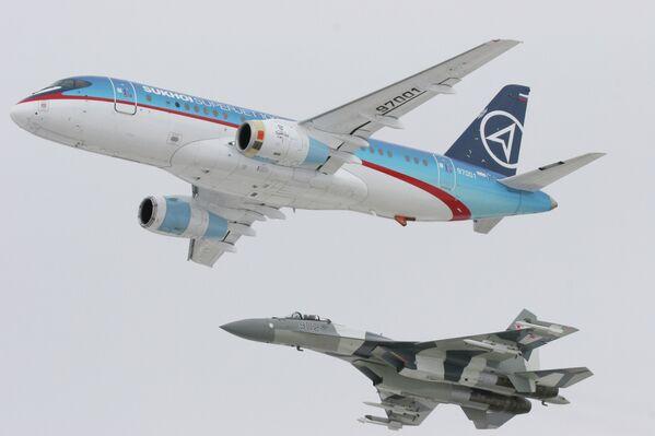 Nuevo avión de pasajeros Sukhoi SuperJet 100 (arriba), escoltado por un caza Su-35. - Sputnik Mundo
