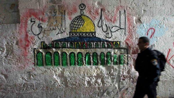 Un policíaco de Israel pasa por el muro con la imagen de la Cúpula de la Roca, Jerusalén - Sputnik Mundo