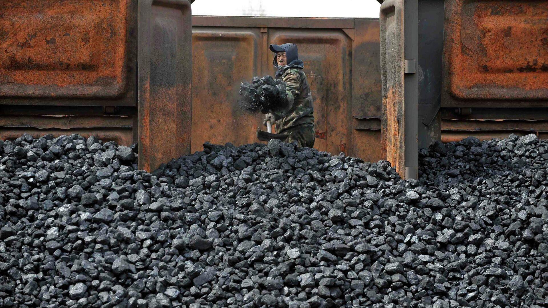 Un trabajador descarga carbón australiano en una estación de tren en Shenyang, China - Sputnik Mundo, 1920, 29.03.2021