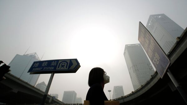 A woman wearing a mask makes her way on a street amid heavy haze and smog in Beijing, in this October 11, 2014 - Sputnik Mundo