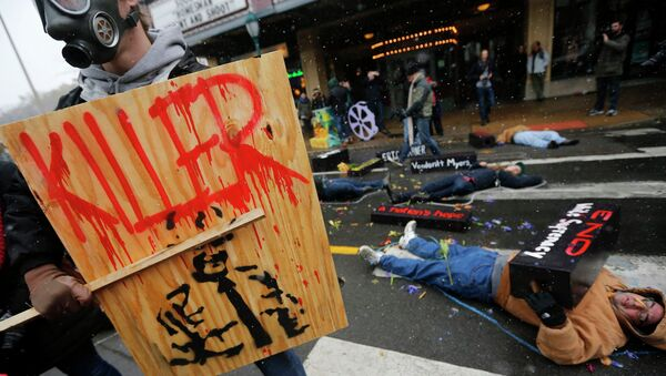 Люди лежат на земле в очерченных мелом контурах во время акции протеста по случаю 100-й день смерти Майкла Брауна - Sputnik Mundo