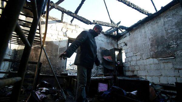 Hombre en su casa dustruida en Donetsk - Sputnik Mundo